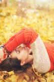 El retrato relajado tranquilo del perfil de la mujer, toma un resto que miente en las hojas de otoño en parque, ojos cerrados Fotografía de archivo libre de regalías