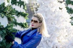 El retrato rubio del ` s en una capa azul en el paisaje del ` s del Año Nuevo Imágenes de archivo libres de regalías