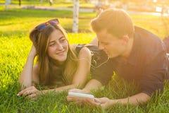 El retrato soleado de la relajación de mentira de los pares jovenes dulces en la hierba junto escucha la música en auriculares en Imágenes de archivo libres de regalías