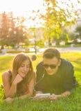 El retrato soleado de la relajación de mentira de los pares jovenes dulces en la hierba junto escucha la música en auriculares en Imagen de archivo