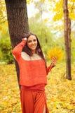 El retrato sonriente bonito de la mujer, caminando en parque del otoño, se vistió en suéter anaranjado casual y falda Foto de archivo libre de regalías