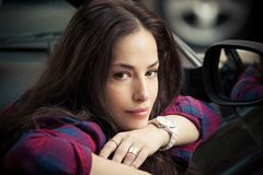 El retrato sonriente de la mujer joven se sienta en el coche que se inclina en ventana Fotos de archivo