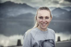 El retrato sonriente rubio joven de la mujer con con las montañas borrosas ajardina en fondo en día cubierto Foto de archivo libre de regalías