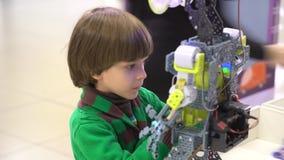 El retrato tiró de muchacho rubio agradable con el destornillador que montaba un robot y que sonreía derecho en la cámara en almacen de metraje de vídeo