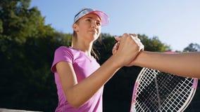 El retrato tirado de la sacudida linda de la muchacha entrega la red de la pista de tenis a otra muchacha almacen de metraje de vídeo