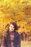 El retrato tranquilo atractivo joven del hombre se vistió en chaqueta gris y el suéter rayado, colocándose en parque del otoño Imagen de archivo