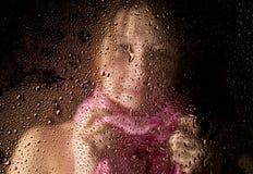El retrato triste joven de la mujer detrás de la ventana en la lluvia con lluvia cae en él Imágenes de archivo libres de regalías