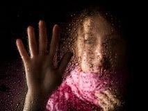 El retrato triste joven de la mujer detrás de la ventana en la lluvia con lluvia cae en él Imagen de archivo