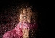El retrato triste joven de la mujer detrás de la ventana en la lluvia con lluvia cae en él Fotografía de archivo libre de regalías