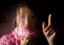 El retrato triste joven de la mujer detrás de la ventana en la lluvia con lluvia cae en él Imagen de archivo libre de regalías