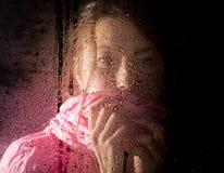 El retrato triste joven de la mujer detrás de la ventana en la lluvia con lluvia cae en él Fotos de archivo libres de regalías