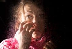 El retrato triste joven de la mujer detrás de la ventana en la lluvia con lluvia cae en él Foto de archivo libre de regalías