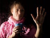El retrato triste joven de la mujer detrás de la ventana en la lluvia con lluvia cae en él Muchacha que sostiene una taza de bebi Imagenes de archivo