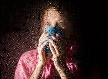 El retrato triste joven de la mujer detrás de la ventana en la lluvia con lluvia cae en él Muchacha que sostiene una taza de bebi Foto de archivo libre de regalías