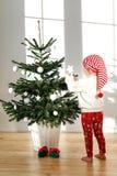 El retrato vertical del pie desnudo de los pequeños standes rubios del niño femenino en piso de madera, adorna el árbol del Año N Fotos de archivo libres de regalías