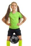 El retrato vertical se divierte a la niña que sostiene la bola entre las piernas Fotografía de archivo libre de regalías