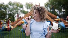 El retrato video de la mujer bonita con el pelo rizado come el caramelo de algodón y sonríe en el parque de atracciones en el ver metrajes