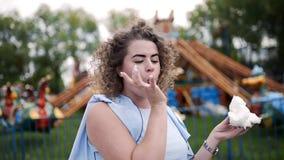 El retrato video de la mujer bonita con el pelo rizado come el caramelo de algodón y sonríe en el parque de atracciones en el ver almacen de video