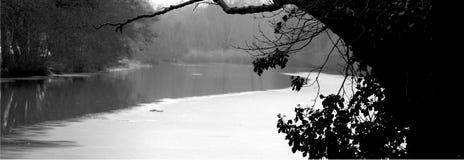 El revoloteo del río congelado parcialmente fotos de archivo
