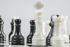 El rey blanco se cae bajo jaque mate de un empeño negro Pedazos de mármol Imagenes de archivo