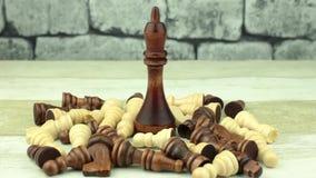 El rey negro grande entre pequeño ajedrez almacen de video