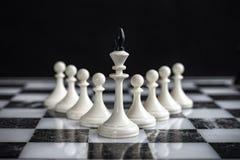 El rey y los empeños en un tablero de ajedrez en un fondo oscuro fotos de archivo libres de regalías