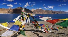 El rezo budista señala el vuelo por medio de una bandera en el lago Pangong, Ladakh, la India Fotografía de archivo