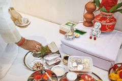 El rezo indio prepraing los artículos de la adoración para el puja de la ceremonia del hilo, pooja con la estatua de Ganesha Fotos de archivo