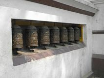 El rezo rueda adentro una pared blanca en SWAYAMBHUNATH STUPA en Katmandu, Nepal Imagenes de archivo