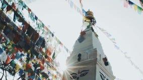 El rezo señala lungta por medio de una bandera en Stupa en luces de la salida del sol metrajes