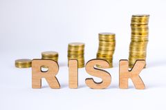 El riesgo de la palabra de letras tridimensionales está en primero plano con las columnas del crecimiento de monedas en fondo bor Imagenes de archivo