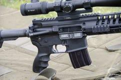 El rifle automático cargado con dios del ` de la munición y de la inscripción bendice el ` de América fotografía de archivo libre de regalías