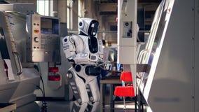 El robot biónico comprueba el equipo de la fábrica, mecanografiando en una tableta almacen de video