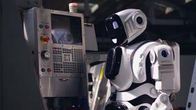 El robot biónico está manejando una consola en una unidad de la fábrica metrajes