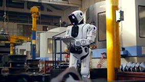El robot biónico está manejando una tableta en la unidad de la fábrica almacen de video