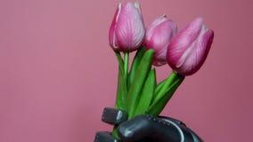 El robot da las flores Los robots dan sostienen tres tulipanes almacen de metraje de vídeo