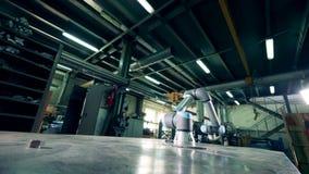El robot de la fábrica está moviendo encendido una tabla en el almacén almacen de metraje de vídeo