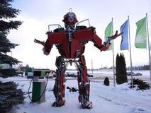 El robot divertido del metal humanoid el autoboat rojo, se hace de recambios del coche, reaprovisiona la gasolina de combustible, foto de archivo