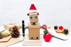 El robot escribirá enhorabuena en la tarjeta con la Navidad y Fotografía de archivo libre de regalías
