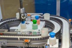 El robot funciona en un transportador para la producci?n de drogas m?dicas imágenes de archivo libres de regalías