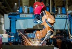El robot industrial está soldando con autógena la parte en fábrica industrial automotriz imagen de archivo libre de regalías
