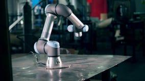 El robot moderno funciona en una fábrica, moviendo encendido una tabla almacen de video