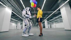 El robot moderno recibe muchos globos de una muchacha almacen de video