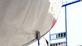 El rodillo con la pintura se desliza sobre el metal de la nave en el astillero en el puerto de Moscú almacen de video