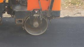 El rodillo de camino rueda el nuevo asfalto almacen de video