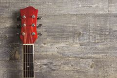 El rojo acústico de la guitarra, cuello que miente en un fondo del vintage de la madera en el fondo del viejo grunge sube Lugar p Imagenes de archivo