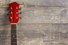 El rojo acústico de la guitarra, cuello que miente en un fondo del vintage de la madera en el fondo del viejo grunge sube Lugar p Foto de archivo