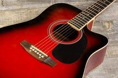 El rojo acústico de la guitarra, cuello que miente en un fondo del vintage de la madera en el fondo del viejo grunge sube Ver Fotografía de archivo
