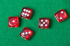 El rojo cinco corta en cuadritos en la tabla verde Foto de archivo