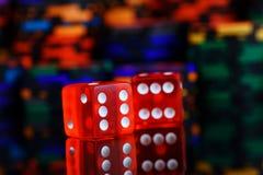 El rojo corta en cuadritos con la reflexión y los microprocesadores del casino en un fondo borroso negro imagenes de archivo